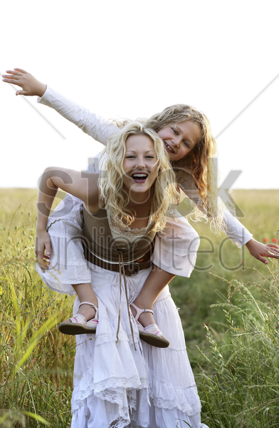 girl on woman's back stock photo