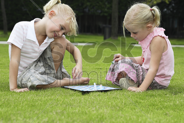 girl playing chess game in the park stock photo