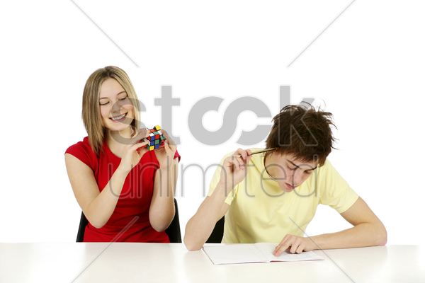 girl playing with cube while boy is doing homework stock photo