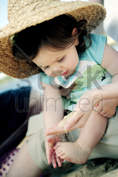 girl playing with sand on the beach stock photo