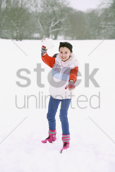 girl playing with snowball stock photo