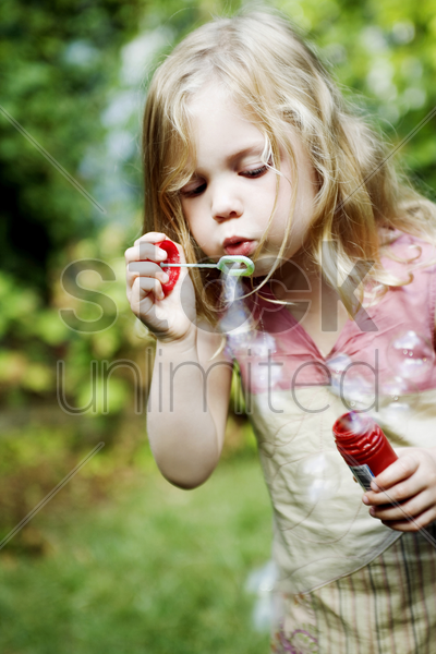 girl playing with soap bubbles stock photo