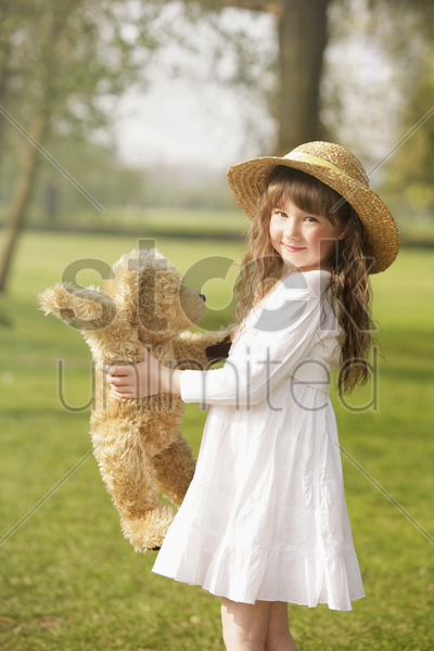 girl playing with teddy bear stock photo