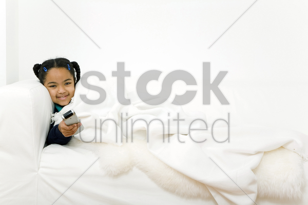girl pointing remote control at the camera stock photo