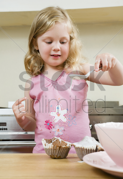 girl pouring flour mixture on cupcakes stock photo