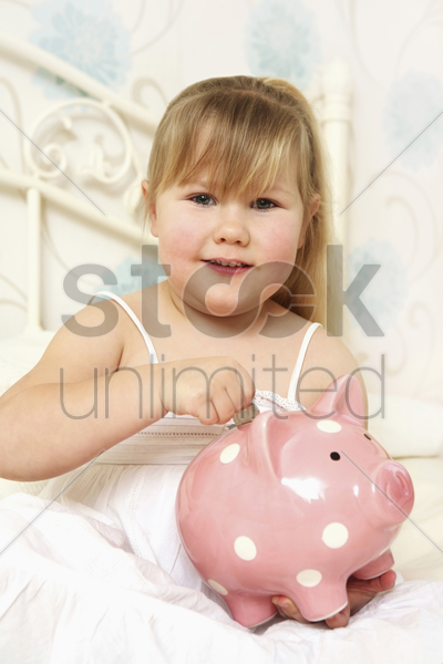 girl putting coin into piggy bank stock photo