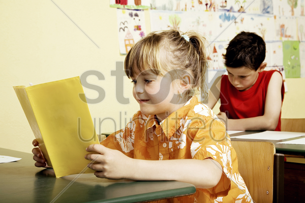 girl reading in the classroom stock photo