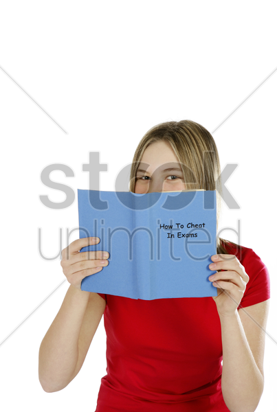 girl reading on ways to cheat in exams stock photo
