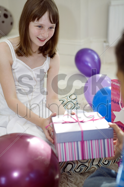 girl receiving present from her friend stock photo