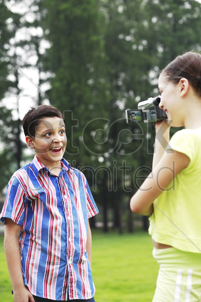 girl recording images of boy making a face stock photo