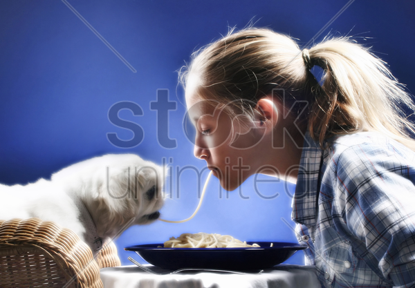 girl sharing spaghetti with her dog stock photo