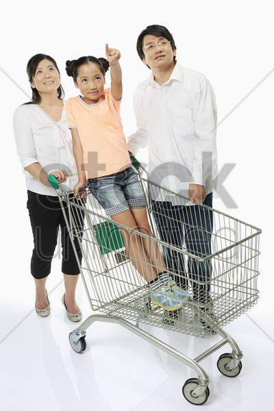 girl showing hand gesture as parents look on stock photo