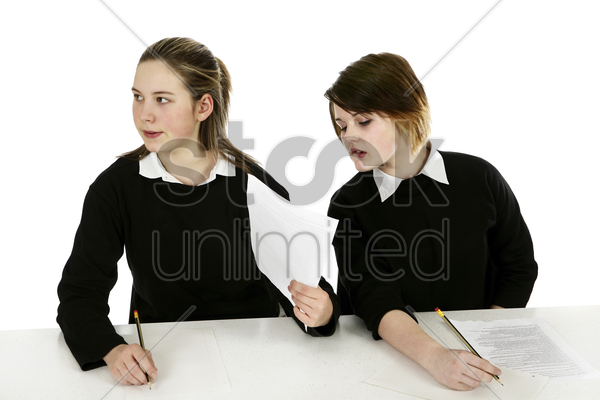 girl showing her answers to her classmate stock photo