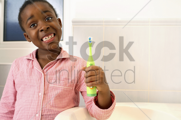 girl showing her teeth while holding a toothbrush stock photo