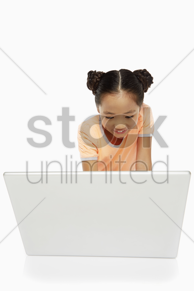girl sitting and using a laptop stock photo