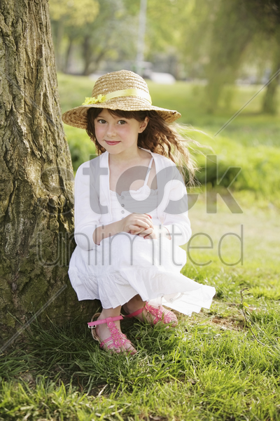 girl sitting by the tree stock photo