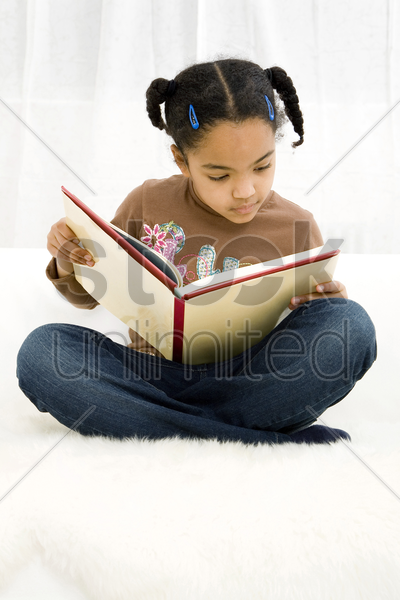 girl sitting on the bed reading book stock photo