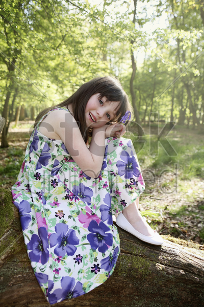 girl sitting on tree root stock photo