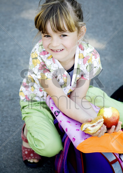 girl squatting down while smiling at the camera stock photo