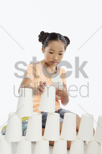 girl stacking up disposable cups stock photo