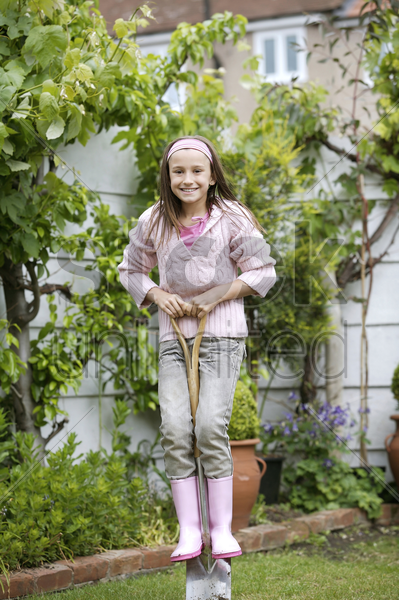 girl standing on a long-handled spade stock photo