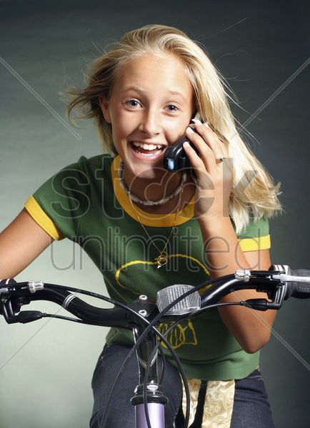 girl talking on the mobile phone while cycling stock photo