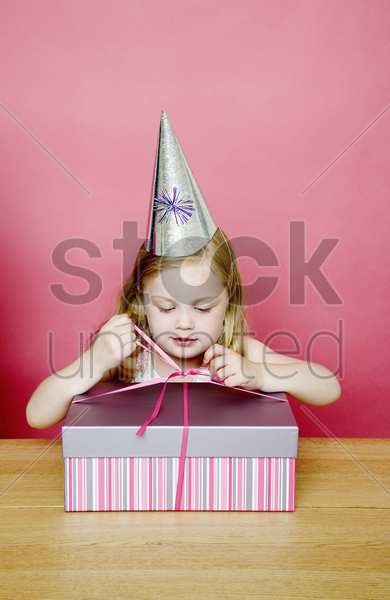 girl unwrapping her present stock photo