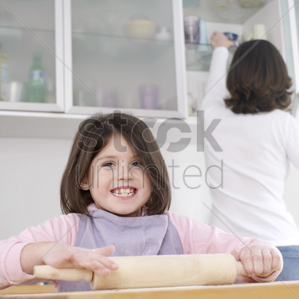 girl using rolling pin with her mother in the background stock photo