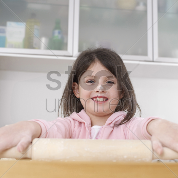 girl using rolling pin stock photo