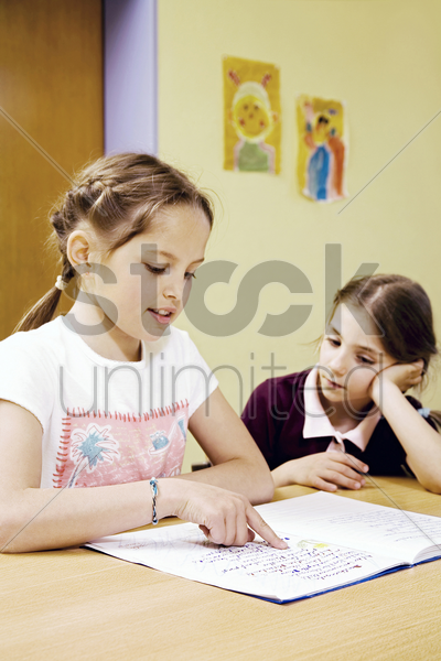 girl watching her friend reading book stock photo