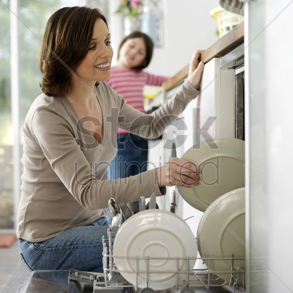 girl watching her mother keeping the dishes in the dishwasher stock photo