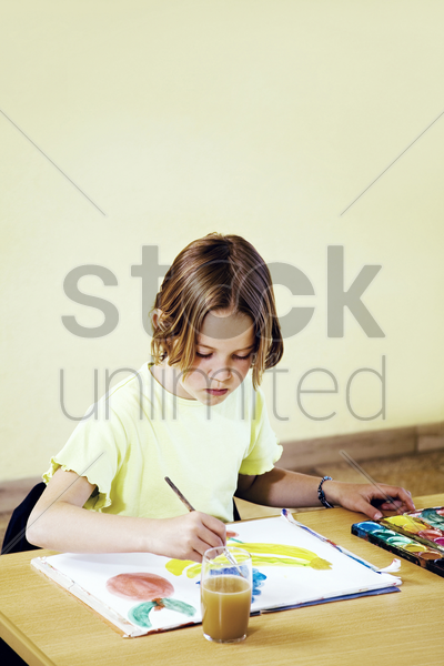 girl water painting in the classroom stock photo