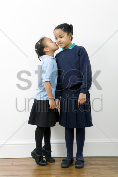 girl whispering into her sister's ear stock photo