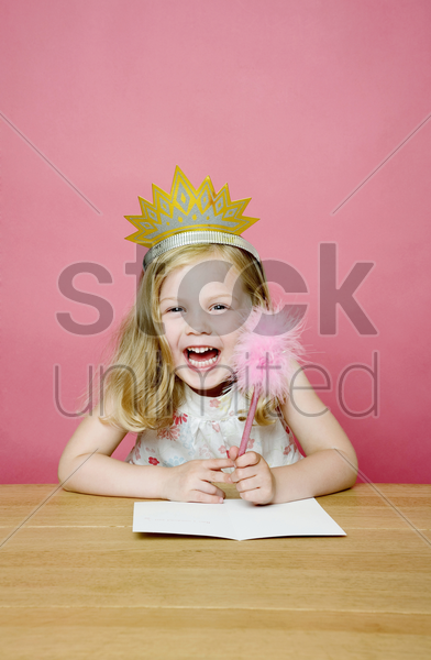 girl with crown smiling while holding a pencil stock photo