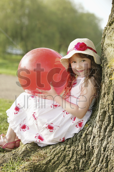 girl with red ball, leaning against tree stock photo