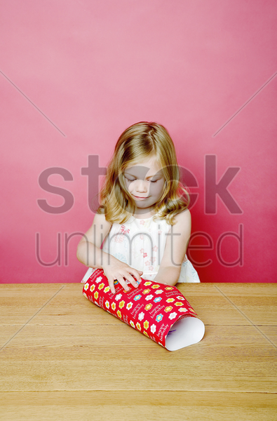 girl wrapping up a present stock photo