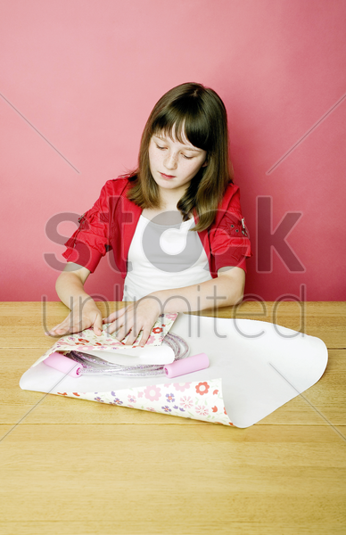 girl wrapping up a skipping rope with a wrapping paper stock photo