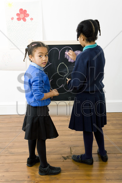 girls colouring a drawing on chalkboard stock photo