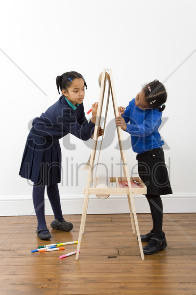 girls drawing on drawing board stock photo