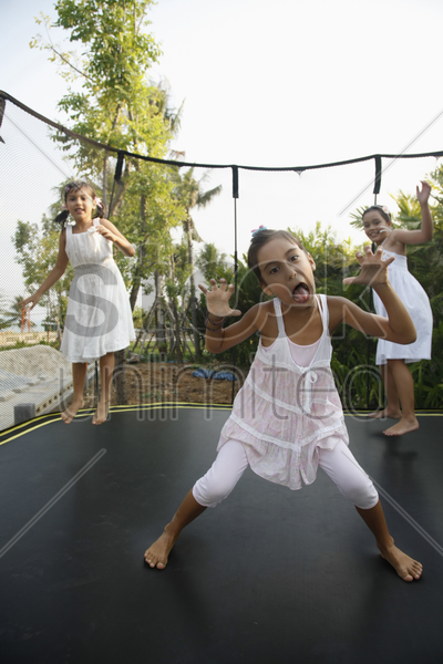 girls jumping on a trampoline stock photo