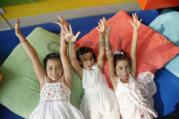 girls lying on pillows with their hands raised stock photo