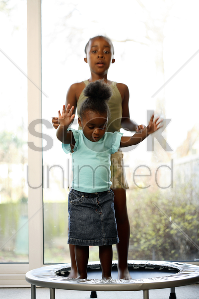 girls playing on trampoline stock photo