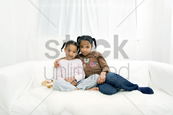 girls posing on the couch stock photo