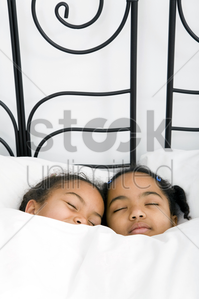 girls sleeping on bed together stock photo