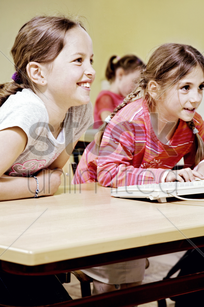 girls smiling while paying attention in the classroom stock photo