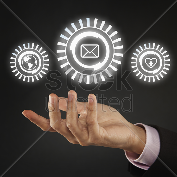 globe, message and heart icon floating above palm stock photo