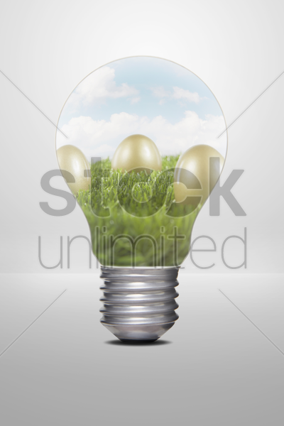 golden eggs placed on grass, inside a light bulb stock photo