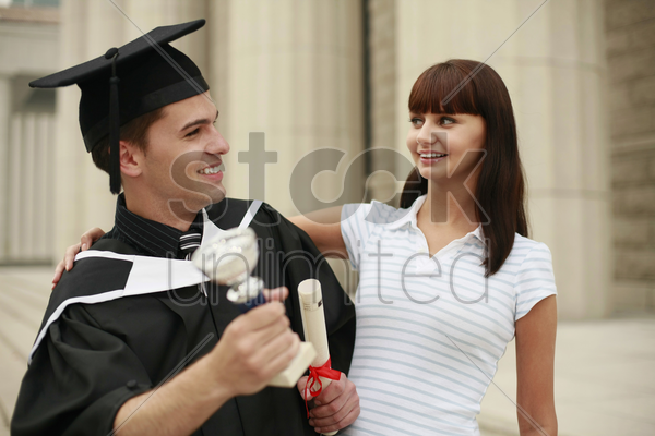 graduate and woman looking at each other stock photo