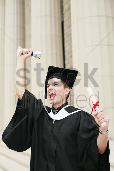 graduate holding up his trophy and scroll stock photo