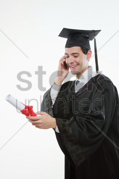 graduate looking at scroll while talking on the mobile phone stock photo